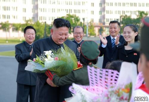 朝鮮少年団第8回大会参加者から花束を受け取る金正恩氏。右端が金与正氏。(2017年6月8日付朝鮮中央通信より)